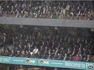 VIPs and dignitaries watch from the tribune as rain lashes down during the memorial service