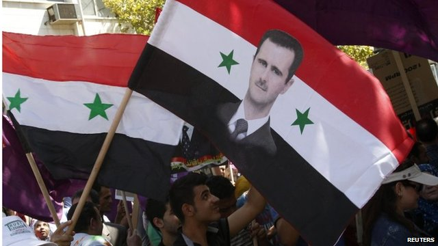 Man waves Syrian flag with image of Bashar al-Assad in Damascus (file photo)