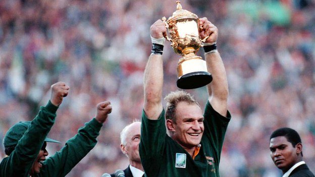 South African rugby captain Francois Pienaar raises the trophy after receiving it from Nelson Mandela (24 June 1995)