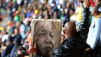 Man raises arm while holding a picture of Nelson Mandela
