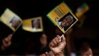 People wave flags at Mandela service