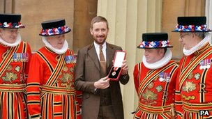 Sir Bradley Wiggins holds his award of a Knighthood
