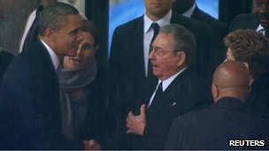 US President Barack Obama (L) shakes hands with Cuban President Raul Castro (C) in this image taken from video courtesy of the South Africa Broadcasting Corporation (SABC) at the FNB stadium in Johannesburg