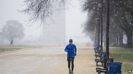 A man jogs on the National Mall near the Washington Monument, background, as snow falls in Washington 10 December 2013