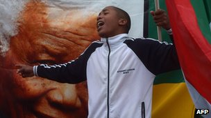 A man waves a South African flag in front of Nelson Mandela's portrait
