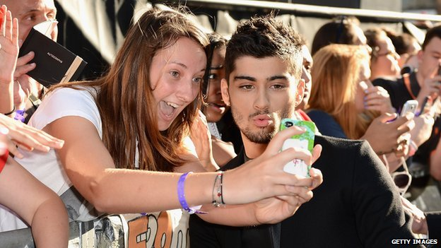 Fan taking a picture with One Direction