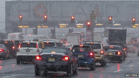 Vehicles wait in line to go through the Holland tunnel to New York City during the arrival of a snowstorm in Newport, New Jersey 10 December 2013