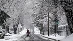 A man walks on a snowy road in Towson, Maryland 10 December 2013