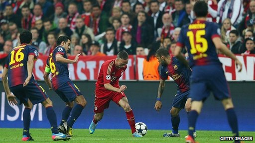 Franck Ribery of Bayern Munich is challenged by Sergio Busquets, Xavi and Daniel Alves