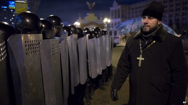 An Ukrainian priest speaks to Riot police as they block Pro-European Union activists camping out in their tents on the Independence Square in Kiev, Ukraine, Wednesday, Dec. 11, 2013
