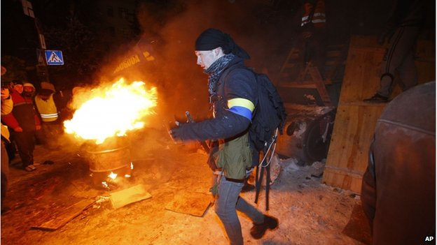 A young man leaves a barricade as riot police try to displace pro-European Union activists from their barricades at the Ukrainian presidential administration building in Kiev, Ukraine, Tuesday, Dec. 10, 2013