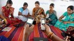 Women using mobile phones in India
