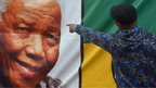 A man points at a portrait of late South African President Nelson Mandela in Soweto on December 10, 2013