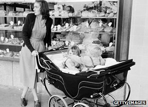 A woman with two children in a pram in 1955