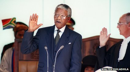 Nelson Mandela raises his right hand as he is speaking