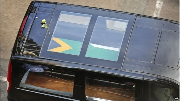 A flower rests on the roof of the car carrying the coffin of Nelson Mandela, December 11