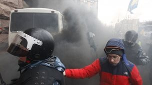 Ukrainian riot police leave a bus after protesters threw a smoke bomb, outside City Hall in Kiev on Wednesday