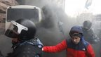 Ukrainian riot police leave a bus after protesters threw a smoke bomb, outside City Hall