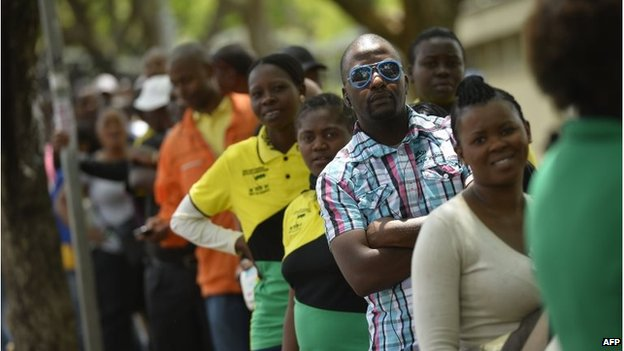 People queue to watch former South African President Nelson Mandela's coffin at the Union Buildings on December 11