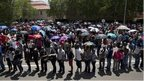 People queue up to get on buses to be taken to Union Buildings