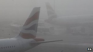 plane seen through fog at heathrow
