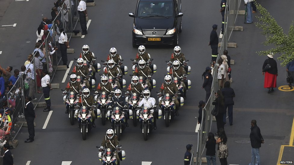Police outriders escort the car carrying Mandela's coffin from the military hospital.