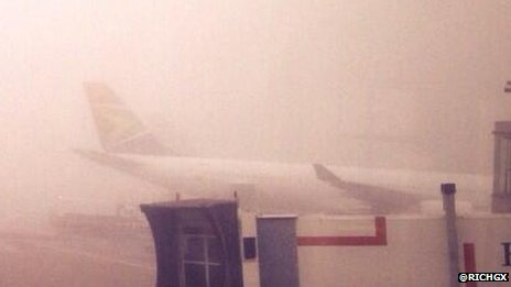 A plane seen through the fog at Heathrow