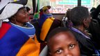 People sit on a bus that will transport them to view the body of Nelson Mandela  on 11 December