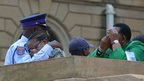 People cry after bidding farewell to South African former president Nelson Mandela lying in state at the Union Buildings in Pretoria on 11 December