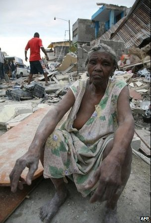 A woman sits in a Port-au-Prince street after the Haitian earthquake, 12 January