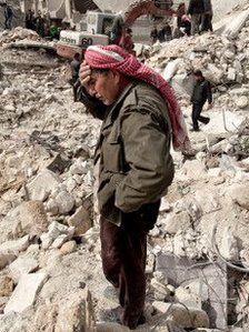 A Syrian man stands in the rubble of his home in Aleppo.