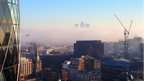 The top of three tall buildings poke out above the fog below. Buildings in the foreground.