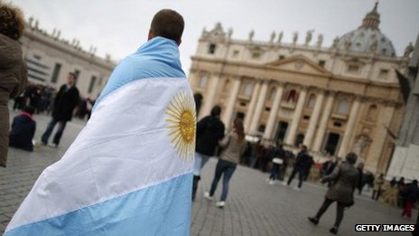 A boy walks in St Peter's Square, draped in the flag of Argentina