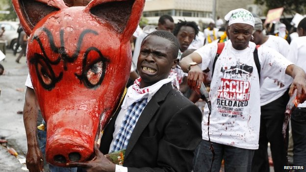 "A protester carries a dummy pig head covered with animal blood, reacts as he participates in a demonstration against lawmakers"" demands for a pay rise"