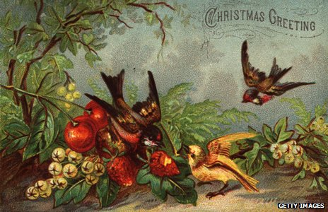 Robins picking strawberries from a bush in this Christmas card from 1880