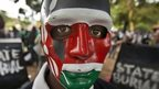 Demonstrator wears a mask in the colours of the Kenyan flag - June 2013