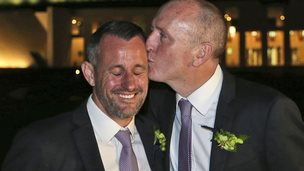 Western Australian politician Stephen Dawson, right, gives his husband Dennis Liddelow a kiss after they married in front of Parliament House in Canberra, Australia, Saturday, Dec. 7, 2013