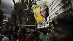 South Africans holding a portrait of Nelson Mandela react as they hear the news that entry to the Union Buildings has closed on December 11, 2013
