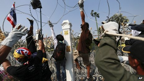 Thai anti-government protesters remove barbed wire erected by Thai police on the fence of Prime Minister's office known as Government House in Bangkok, Thailand 12 December 2013