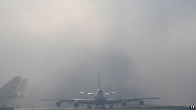 planes seen through fog at heathrow's terminal five
