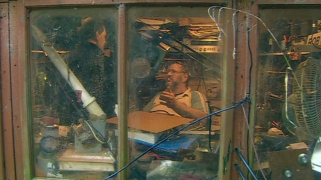 Radio enthusiast in shed full of equipment