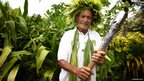 An elder in a traditional floral headdress holds the Queen's Baton in Rarotonga, Cook Islands.