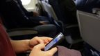 Woman uses phone on plane