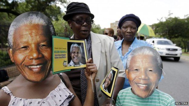 A boy and a girl wear masks of former South African President Nelson Mandela as they queue to view his body