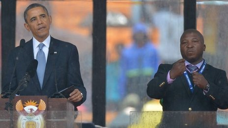 US President Barack Obama delivers a speech at the Nelson Mandela memorial next to sign language interpreter Thamsanqa Dyantyi