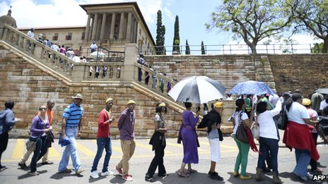 South Africans stand in line to pay their respect to South African former president Nelson Mandela laying in state at the Union Buildings on December 12, 2013 in Pretoria