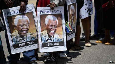 People hold portraits of Nelson Mandela as South Africans stand in line to pay their respect to South African former president Nelson Mandela laying in state at the Union Buildings on December 12, 2013