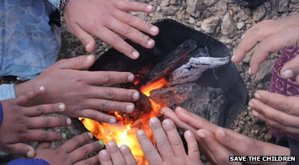 Children's hands around a fire