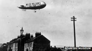 """Walter Willson's on top"" slogan on side of airship over a North East town"