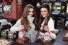 Cheryl Cole (left) stands behind the bar on set of Coronation Street with Michelle Keegan.